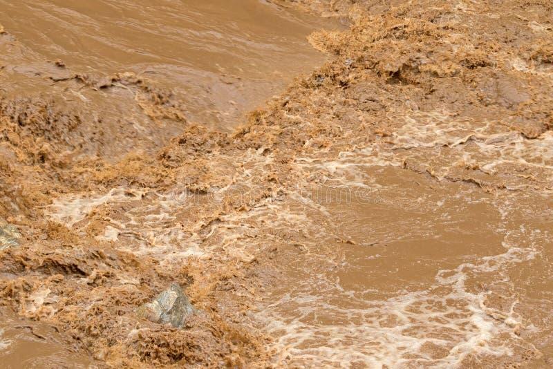 Close-up van snelle stroom van bruin water in de modderige rivier stock afbeelding