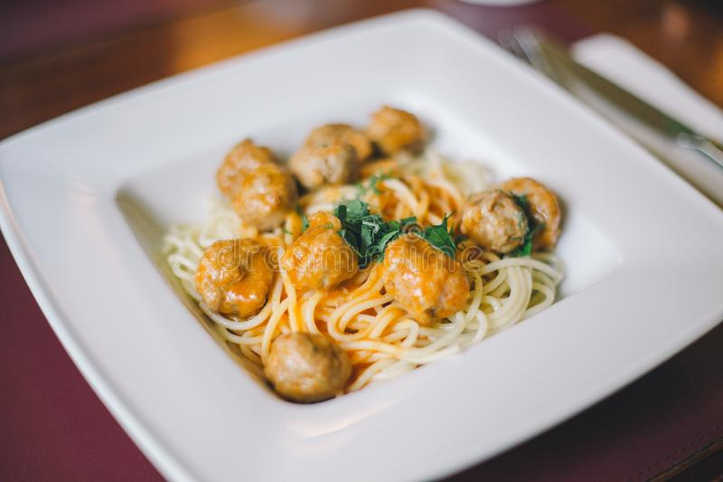 Close-up van spaghettideegwaren met vleesballetjes en tomatensaus in een witte plaat op de lijst stock afbeeldingen