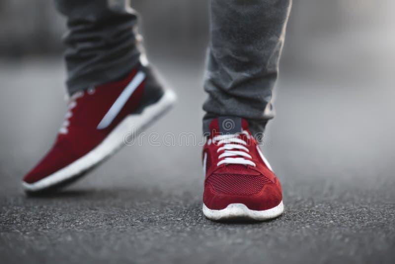 Close-up van sporten het rode tennisschoenen op asfalt Benen en schoenen vanuit de lagere invalshoek stock foto