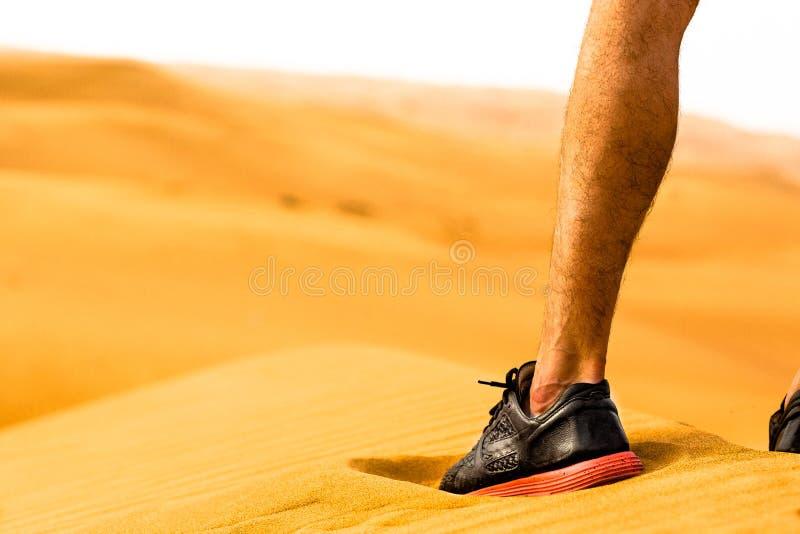 Close-up van sportief mensenbeen/schoen die zich alleen in de woestijn bevinden Het concept van de geschiktheid stock foto