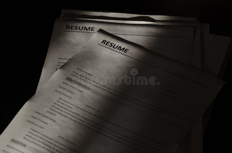 Close-up van stapel samenvattingstoepassingen op donkere oppervlakte, zwarte schaduwen Concept het houden van kandidaten in een s stock foto's