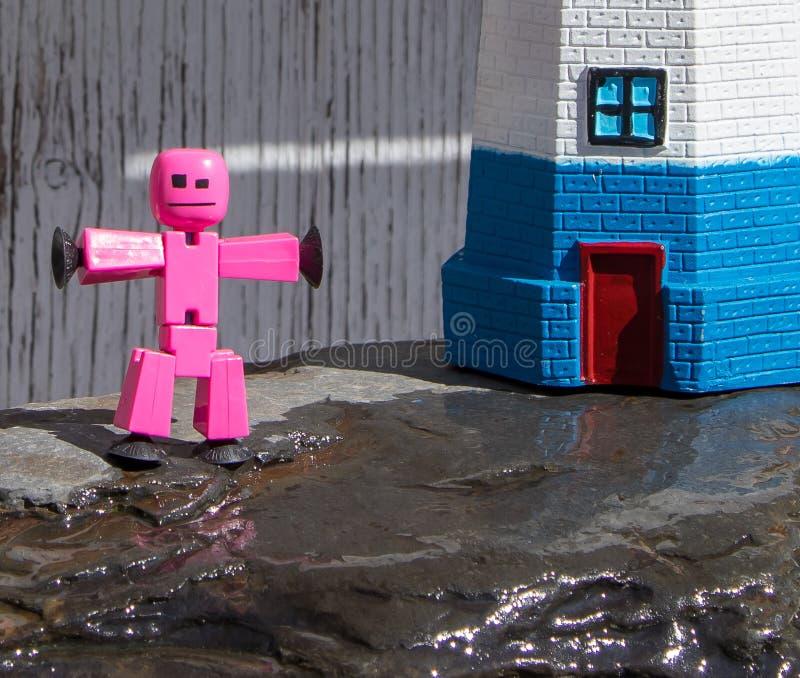 Close-up van stuk speelgoed stokcijfer het spelen op natte rotsen stock foto's