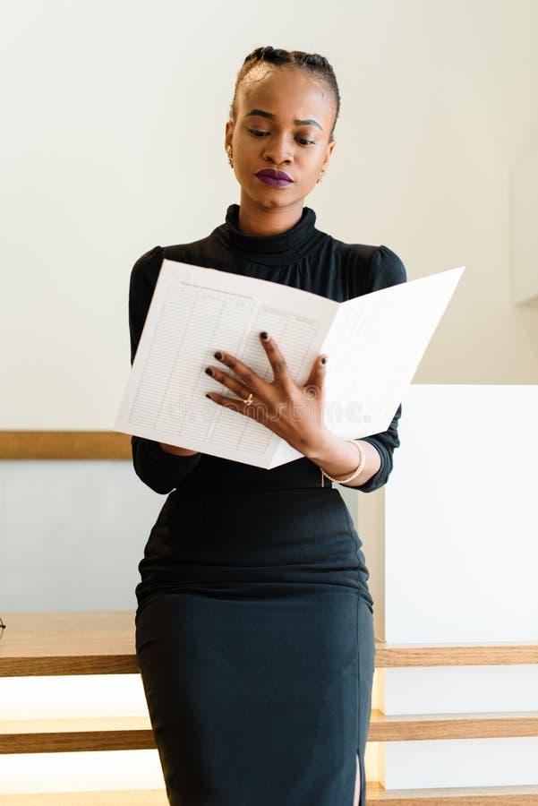 Close-up van succesvolle Afrikaanse of zwarte Amerikaanse het bedrijfsvrouw holding en bekijken groot wit dossier stock afbeelding