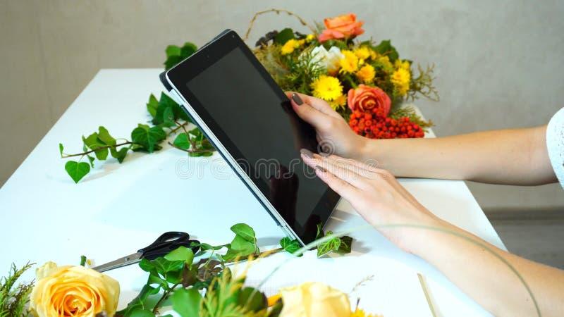 Close-up van tablet waarop de handen van het bloemistmeisje ` s vingers am leiden stock afbeeldingen