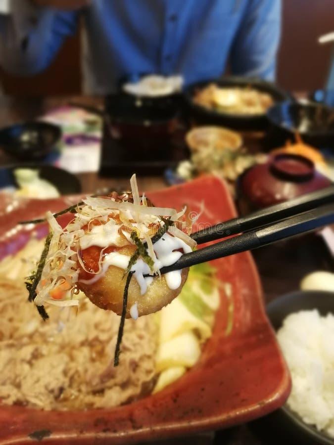 Close-up van takoyaki, Eetstokje vastgeklemde takoyakibal stock foto