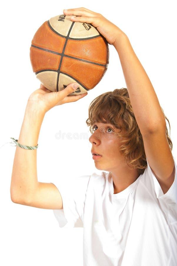 Close-up van tiener die basketbal werpen stock afbeelding