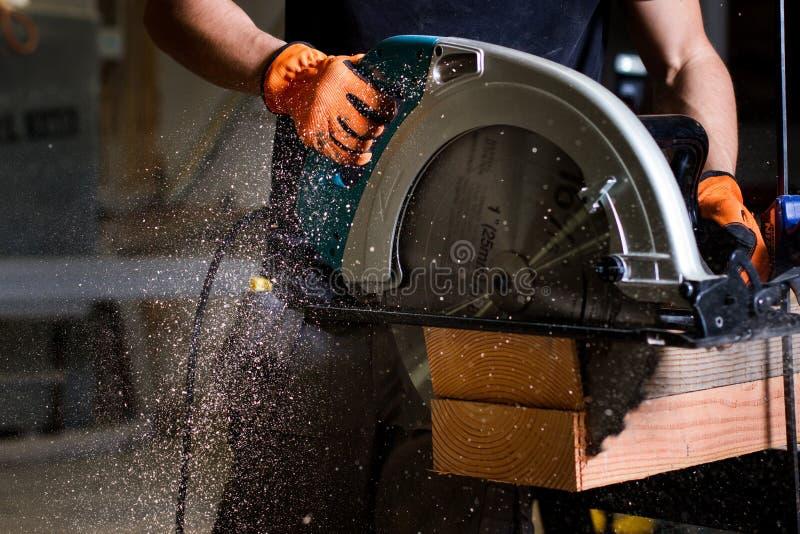 Close-up van timmerman die elektrische cirkelzaag gebruiken om houten planken te snijden stock foto's