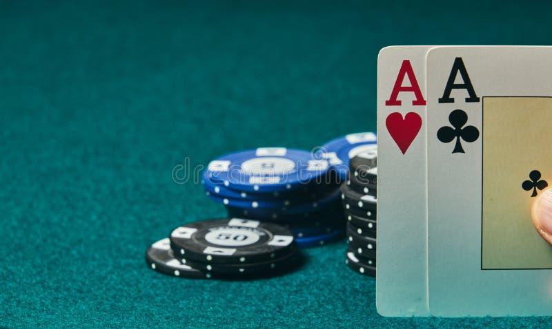 close-up van twee azen die in één hand op de groene spelmat worden gehouden op de rechterkant van het beeld om plaats te verlaten royalty-vrije stock foto