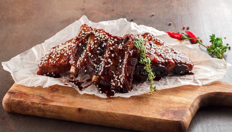 Close-up van varkensvleesribben met BBQ saus worden geroosterd en gekarameliseerd in honing op een bed van arugula die Smakelijke royalty-vrije stock fotografie