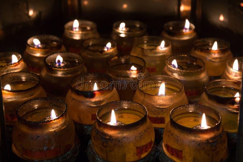 Close-up van vele brandende kaarsen stock afbeelding
