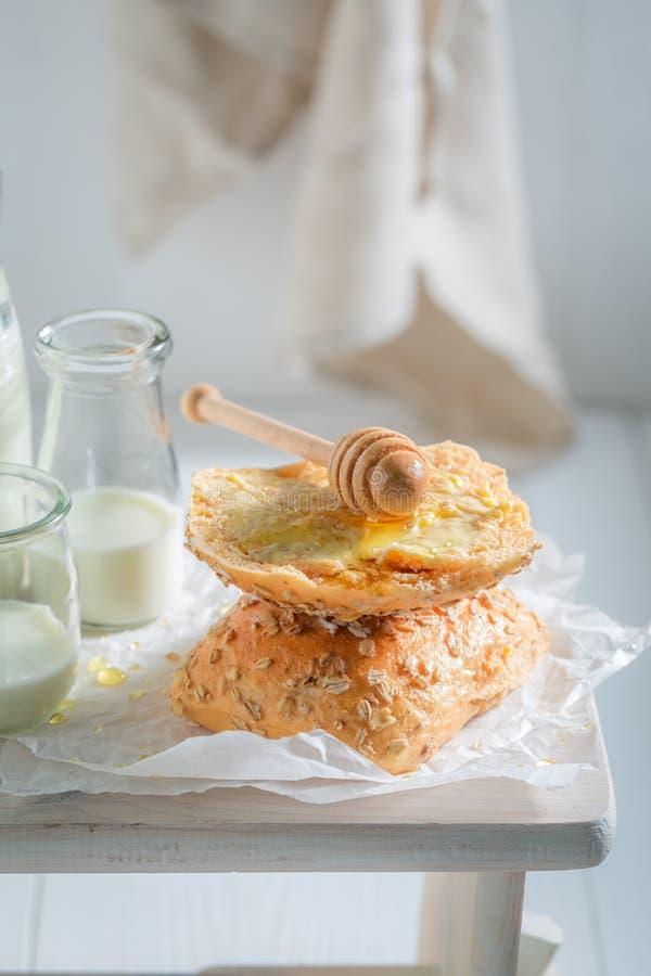Close-up van vers broodje met honing en melk voor ontbijt stock foto's