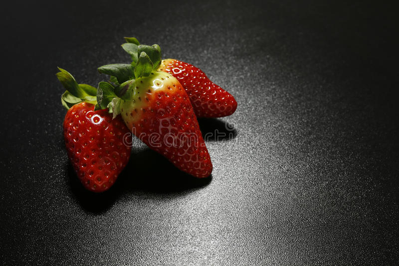 Close-up van verse aardbeien op zwarte achtergrond royalty-vrije stock afbeelding