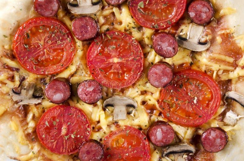 Close-up van verse voorbereide en hete pizza met paddestoelen, tomaten, kaas, geroosterde worst en tomatensaus stock foto's