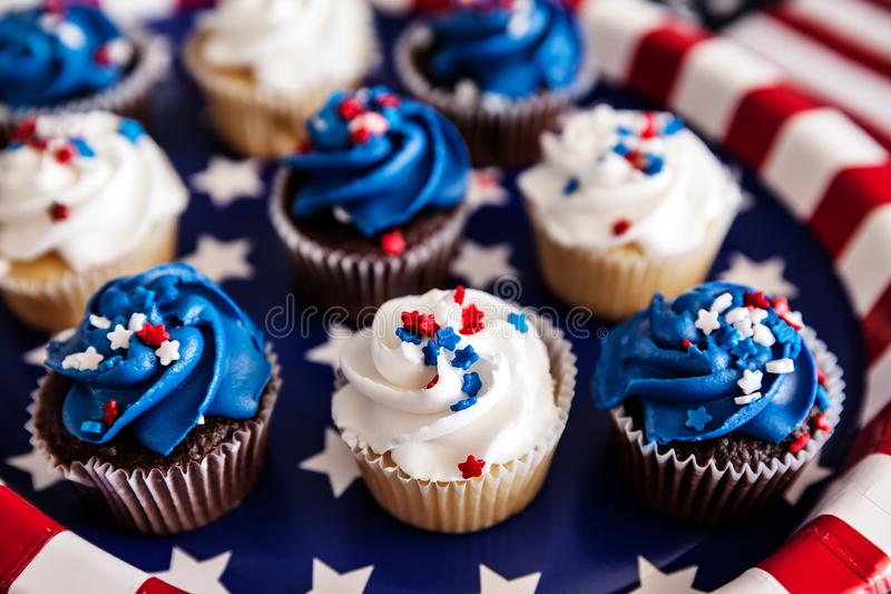 Close-up van Vierde van Juli cupcakes met een Amerikaanse vlag op een achtergrond, selectieve nadruk stock afbeelding