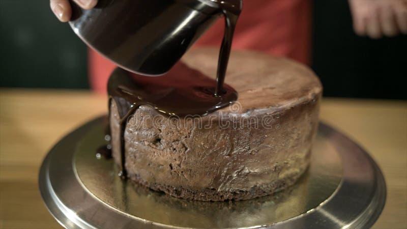 Close-up van vloeibare die chocolade op cake wordt gegoten actie De gesmolten vloeibare chocolade spreidt over ronde cake op ijze stock fotografie