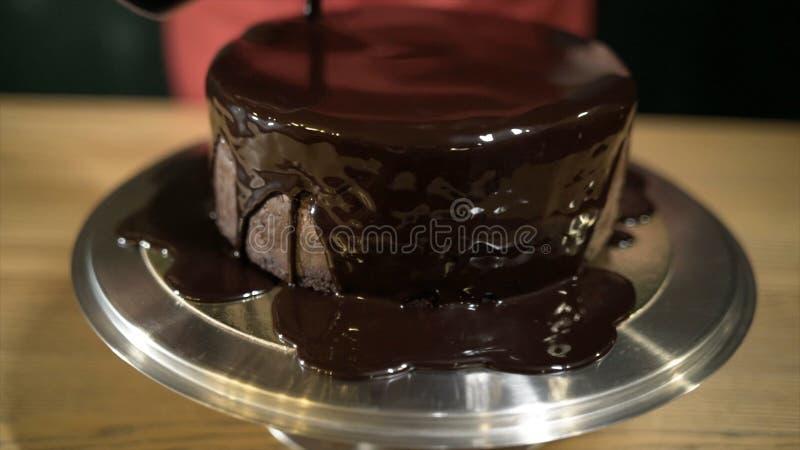Close-up van vloeibare die chocolade op cake wordt gegoten actie De gesmolten vloeibare chocolade spreidt over ronde cake op ijze royalty-vrije stock afbeelding
