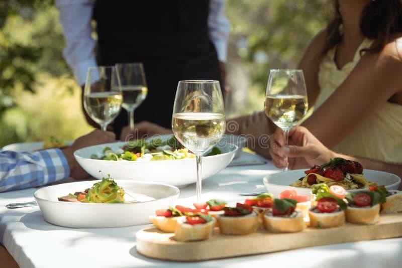 Close-up van voedsel en wijnglas op eettafel royalty-vrije stock foto's