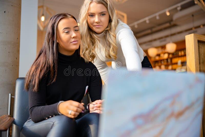 Close-up van Vrienden die Schoolwork op Laptop doen bij Restaurant in Stad stock afbeelding
