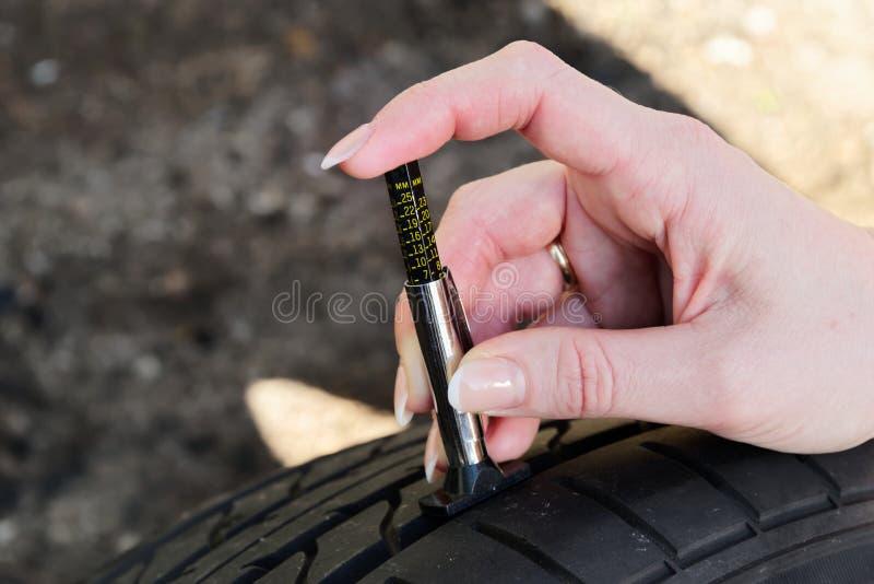 Close-up van vrouw die loopvlak controleren op autoband met maat royalty-vrije stock afbeelding