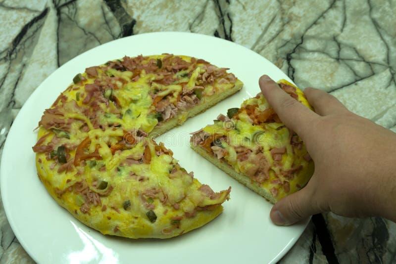 Close-up van vrouw die plak van mozarella kaasachtige pizza thuis met de hand plukken op houten pan Eigengemaakte pizza stock foto