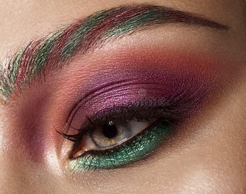 Close-up van vrouwelijk oog met kleurrijke van ogenschaduwen en wimpers make-up wordt geschoten die royalty-vrije stock foto's