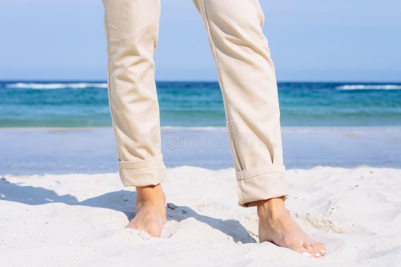 Close-up van vrouwelijke benen in beige broek blootvoets op het strand royalty-vrije stock afbeelding
