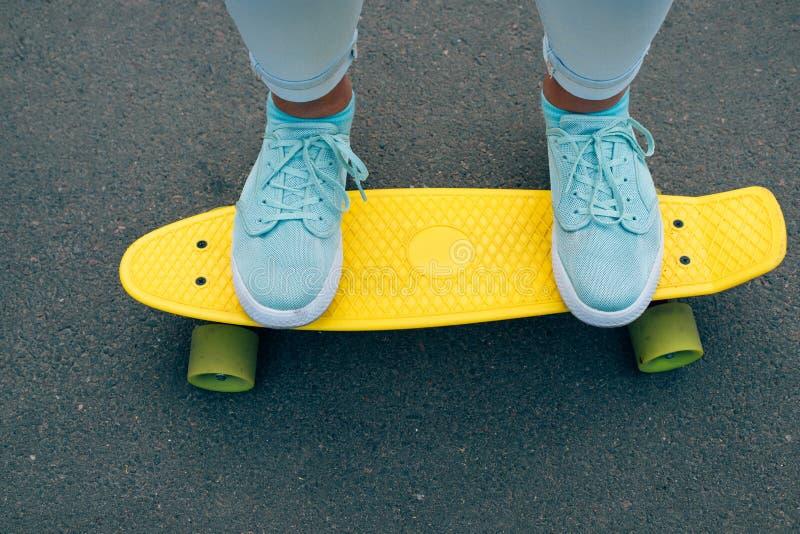 Close-up van vrouwelijke benen in jeans en blauwe tennisschoenen die zich op a bevinden stock foto