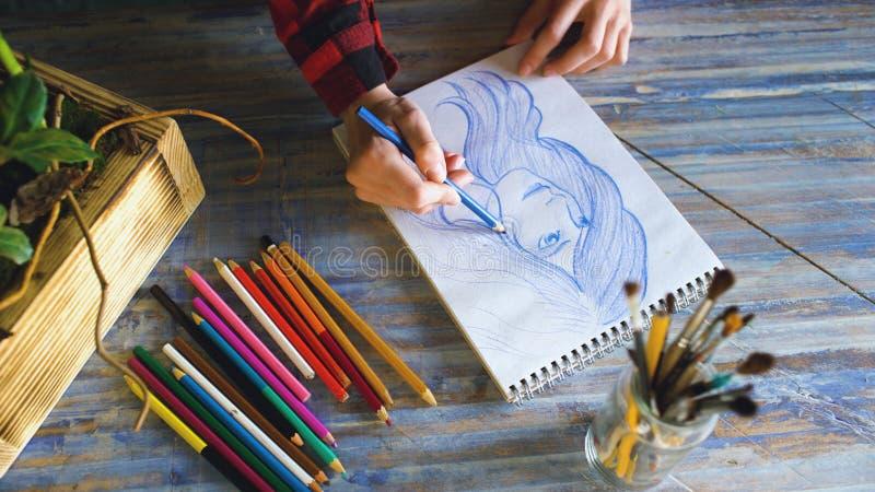 Close-up van vrouwelijke hand het schilderen schets op document notitieboekje met potloden Vrouwenkunstenaar op het werk royalty-vrije stock foto's