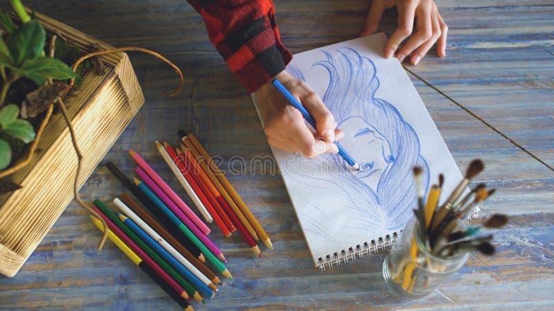 Close-up van vrouwelijke hand het schilderen schets op document notitieboekje met potloden Vrouwenkunstenaar op het werk stock fotografie