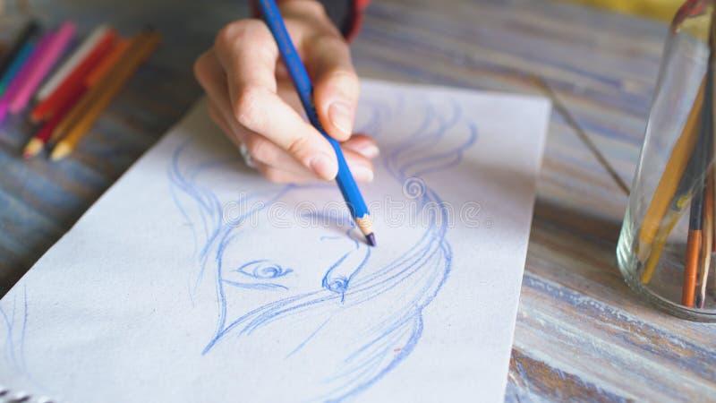 Close-up van vrouwelijke hand het schilderen schets op document notitieboekje met potloden Vrouwenkunstenaar op het werk stock foto's