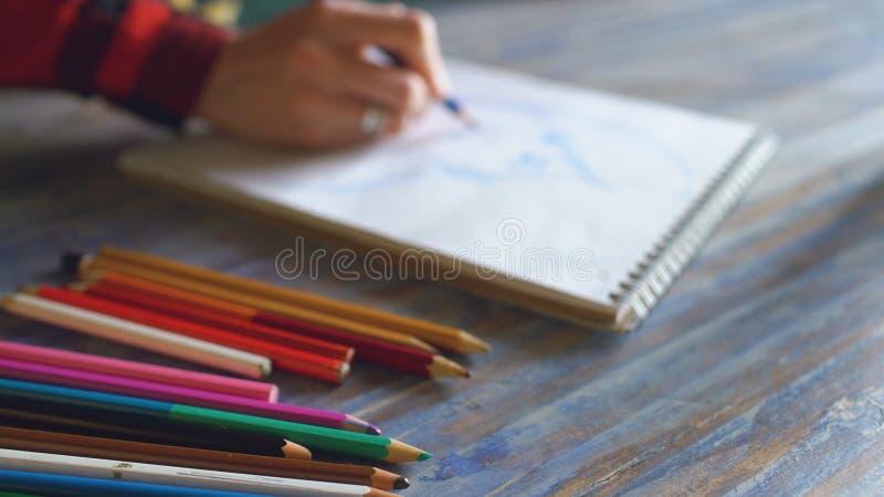 Close-up van vrouwelijke hand het schilderen schets op document notitieboekje met potloden Vrouwenkunstenaar op het werk royalty-vrije stock foto