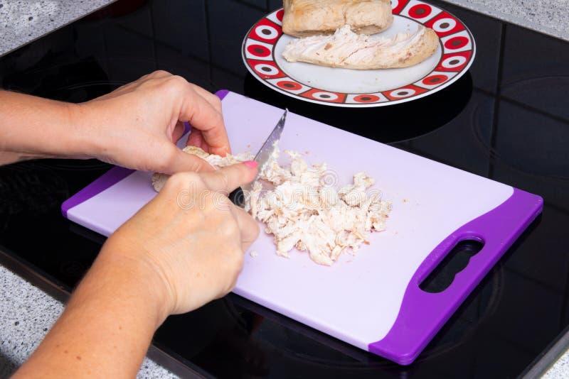 Close-up van vrouwelijke handen met een mes in hun handen dat het gekookte vlees van Turkije op een scherpe raad snijdt Concepten stock foto