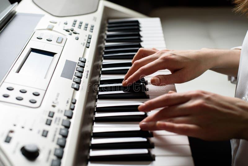 Close-up van vrouwelijke handen op de elektronische piano in de stijl van Dode Pan stock fotografie