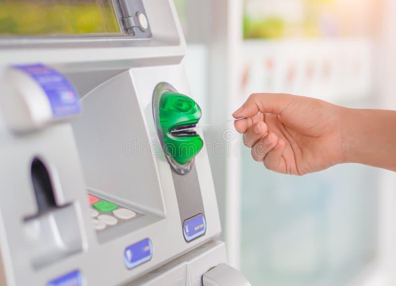 Close-up van vrouwen` s hand die debetkaart opnemen in ATM machin stock foto