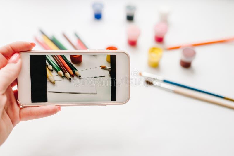 Close-up van vrouwen` s handen die foto op mobiele telefoon maken: werkruimte van kunstenaar voor tekening: kleurpotloden, waterv royalty-vrije stock afbeeldingen