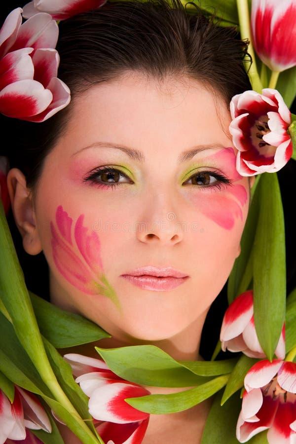 Close-up van vrouwengezicht frame met tulpen stock afbeeldingen
