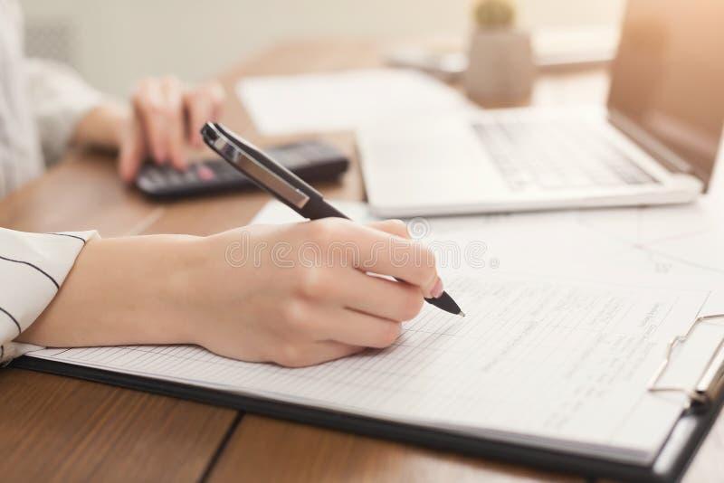 Close-up van vrouwenhand die in documenten schrijven en calculator gebruiken royalty-vrije stock afbeelding