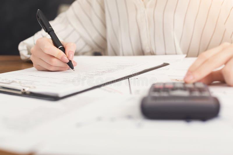 Close-up van vrouwenhand die in documenten schrijven en calculator gebruiken stock fotografie