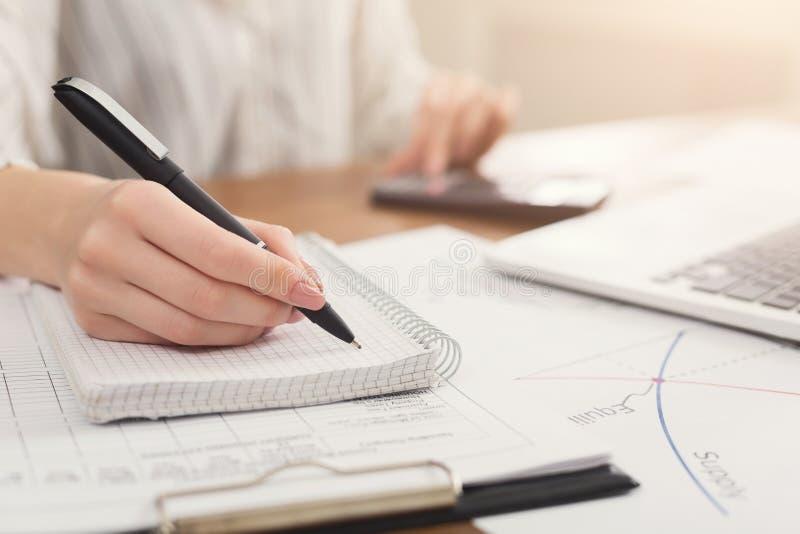 Close-up van vrouwenhand het schrijven nota's en het gebruiken van calculator royalty-vrije stock afbeeldingen