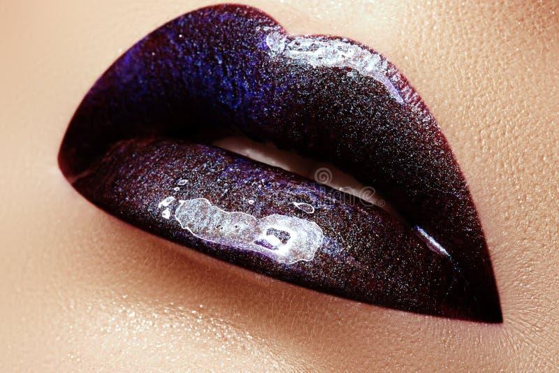 Close-up van vrouwenlippen wordt geschoten met glanzende pruimlippenstift die Perfect p stock afbeelding