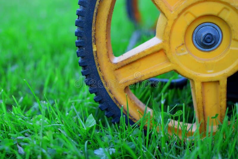 Close-up van vuil geel wiel van grasmaaier stock fotografie