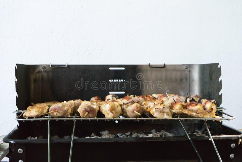 close-up van wat vlees op Houten vleespennen die in een barbecue worden geroosterd Roosteren gemarineerd shashlik op een steenkoo royalty-vrije stock afbeelding