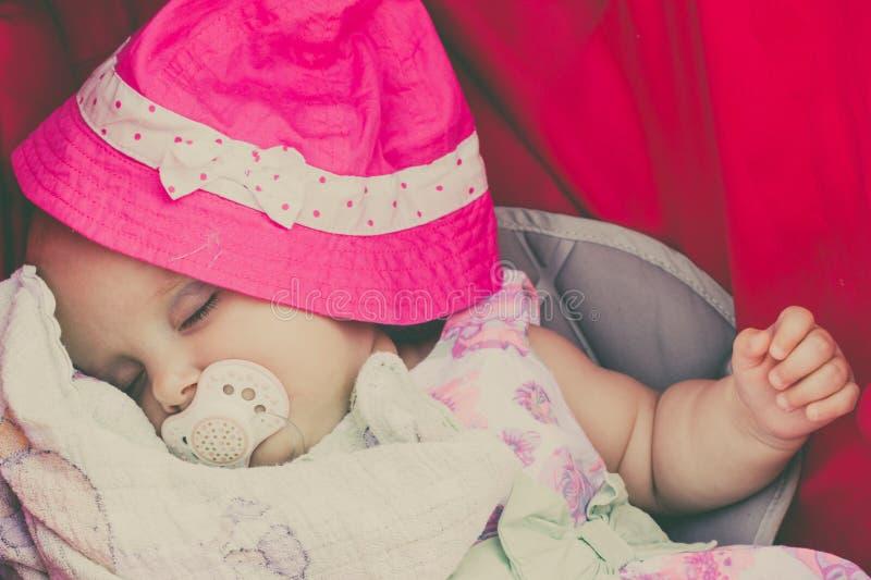 Close-up van weinig baby omvat met roze hoed stock foto's