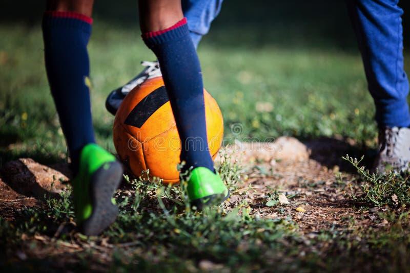 Close-up van weinig speelvoetbal van het jongensbeen op voetbalhoogte Voetbal, voetbal Opleiding op een voetbalgebied royalty-vrije stock foto's