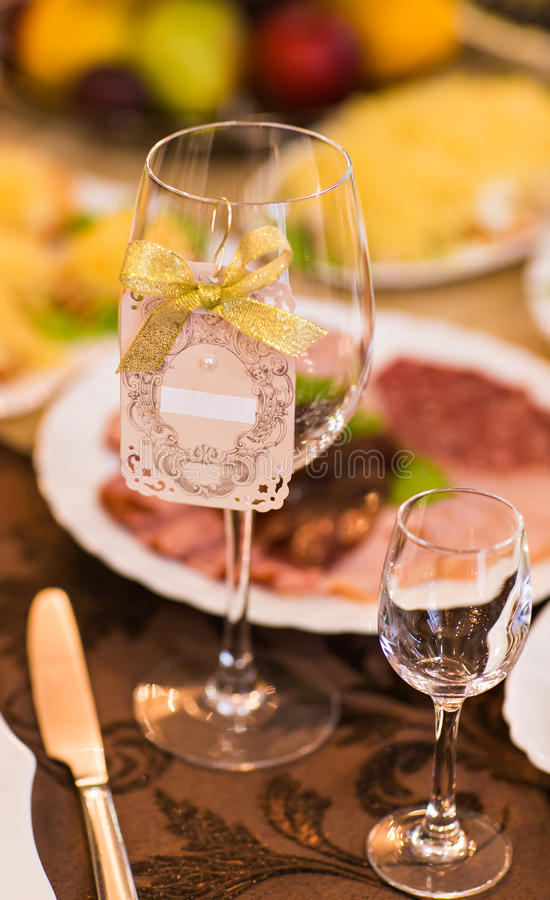 Close-up van wijnglas en naamkaart op feestelijke lijst stock foto