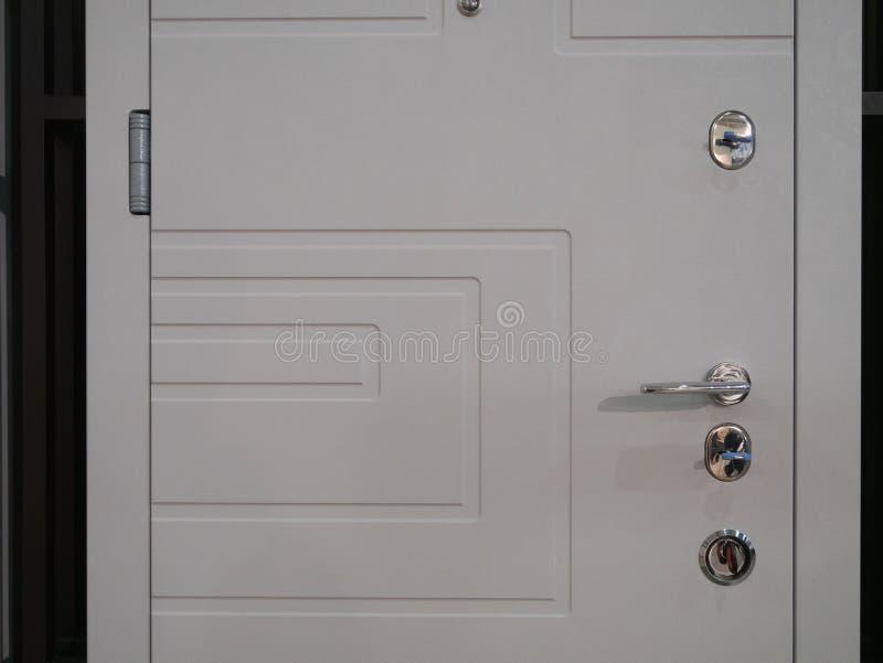 Close-up van witte ingangs moderne gepantserde voordeur met weinig sloten en handvat stock foto's