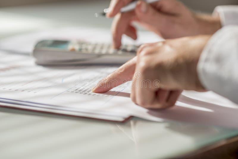 Close-up van zakenman of accountant die gegevens en aantallen controleren royalty-vrije stock fotografie