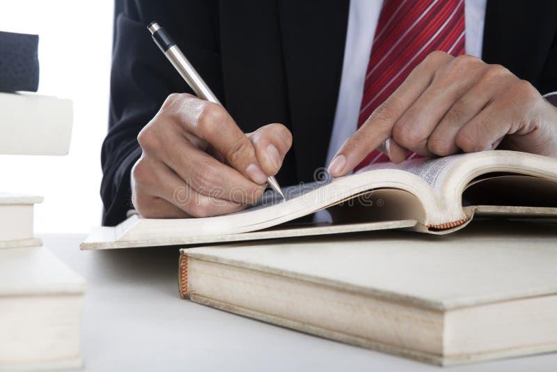 Close-up van zakenman het schrijven op een boek royalty-vrije stock afbeeldingen