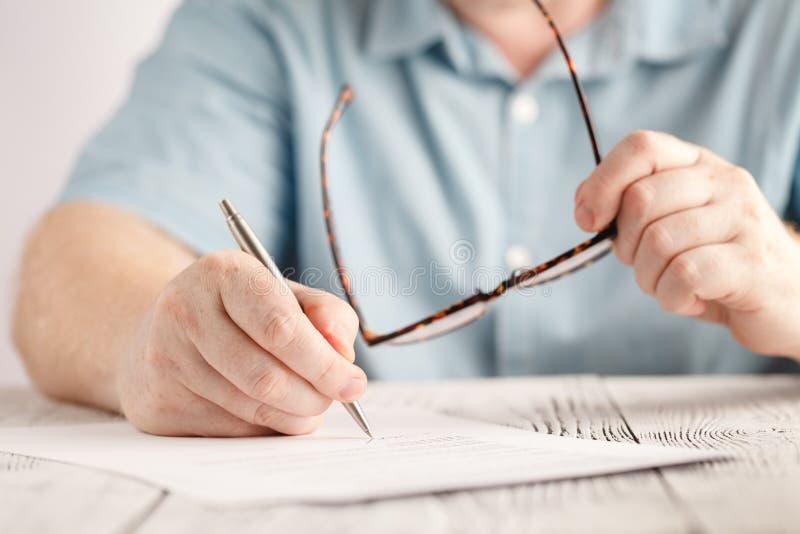 Close-up van zakenmanhanden die iets op stuk van document schrijven en paar glazen houden stock foto