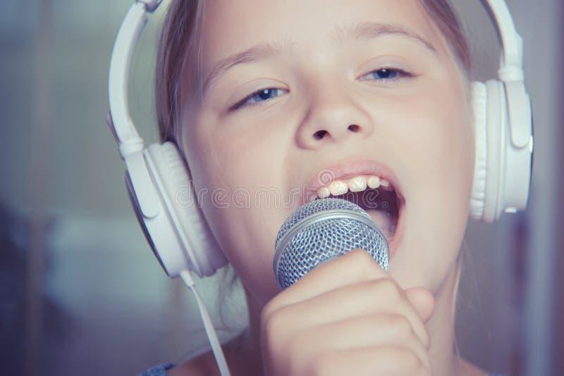 Close-up van zingend Kaukasisch kindmeisje Het jonge meisje zingt emotioneel in de microfoon, houdend het met hand stock fotografie